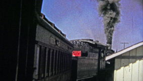 1972: Polluting old coal firing train pulling out of the station. stock footage