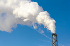 Polluting smoke coming out of chimney Stock Image