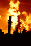 Pollution. Backlit silhouettes of smoke stacks of a coal-burning power plant Royalty Free Stock Photo