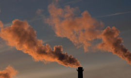 Pollution. Spewing into the air from industrial chimney Royalty Free Stock Photos