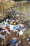 Pollution. Water pollution, plastic bottles and garbage on river shore Royalty Free Stock Image
