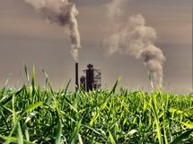 Pollution. A grass field and a industry Stock Photo