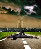 Pollution. Dead man on the street and a factory