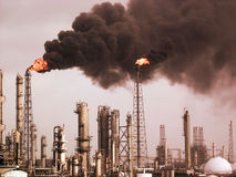 Pollution. Refinery in an upset condition flaring heavily and causing pollution against a stormy background