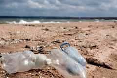 Pollution on beach – plastic cans Royalty Free Stock Photo