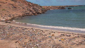 Pollution on a beach. Articles washed ashore on a beach on Bonaire, The Netherlands stock footage