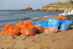 Pollution on the Beach. With Colorful Plastic Bags Royalty Free Stock Photos