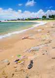Pollution on the beach of tropical sea. Royalty Free Stock Image