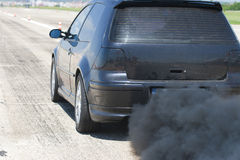 Pollution car. Pollution of environment by combustible gas of a black car Royalty Free Stock Image