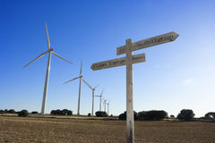 Pollution-Clean Energy cross road sign with windmills in the bac Royalty Free Stock Photos