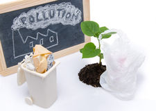 Pollution concept with a green small plant, a plastic bag and a Royalty Free Stock Image