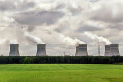 Pollution. Environmental problem. Factory chimneys (pipes) polluting air on a green field. Stock Images