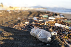 Pollution - plastic water bottle on a beach. Pollution - plastic water bottle and other garbage on a beach during sunset Royalty Free Stock Photo