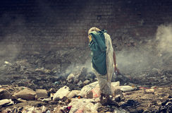 Pollution and poverty. Indian old female searching food for herself in  garbage Stock Image