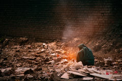 Pollution and poverty. Indian old female sitting  for warmup  herself near fire in garbage Royalty Free Stock Photos