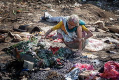 Pollution and poverty. Indian old female sitting  for warmup  herself near fire  in  garbage Stock Photography