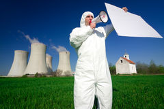 Pollution Protester. A environmental activist protesting with a blank banner in front of nuclear power plant stock image