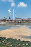 Pollution in the sea. Polluted water with a large steel plant in the background stock photos
