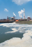 Pollution in the sea. Polluted water with a large steel plant in the background stock photography