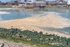 Pollution in the sea. Polluted water with a large steel plant in the background royalty free stock photo