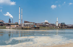 Pollution in the sea. Polluted water with a large steel plant in the background stock image