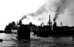 Pollution of ships in the port. Civitavecchia rome italy some ships pollute with their engines lit the city sky. Dense black smoke comes out of their chimneys royalty free stock photos