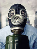 Pollution in town. Businessman with gas mask and town background stock photos