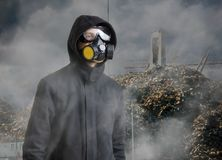 Pollution and toxic waste concept. Man with gas mask in front of landfill Royalty Free Stock Photo
