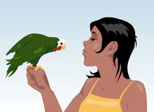 Polly's kiss. Young tanned brunette playing with a green parrot