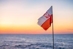 Polnische Flagge des Rotes und des Weiß an der Dämmerung Stockfotos