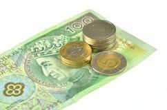 Polnische Münzen auf 100 pln Banknote Stockbild