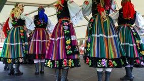 Polnische Tänzer der Frau in den traditionellen Folklorekostümen auf Stadium Stockfotos