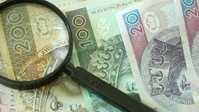 Polnische Zlotybanknoten mit Vergrößerungs-glas stock video footage