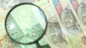Polnische Zlotybanknoten mit Vergrößerungs-glas stock video