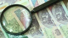 Polnische Zlotybanknoten mit Vergrößerungs-glas stock footage