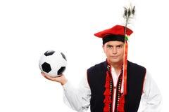 Polnischer Mann in einer traditionellen Ausstattung mit Fußball Stockbild