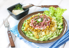 Polnischer Salat mit Kartoffeln, Schinken, Gurke, grüne Erbsen, Kapriolen Stockbild