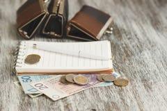 Polnischer Zloty mit kleinen Geldbörsen und Notizbuch auf dem hölzernen Hintergrund Lizenzfreie Stockfotos