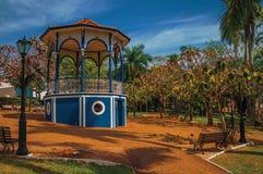 Polo colorido viejo del gazebo y de iluminación en el medio del jardín verde, en un día soleado en São Manuel Foto de archivo