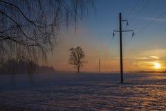 Polo de alto voltaje en la puesta del sol del invierno del campo fotos de archivo libres de regalías