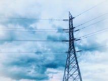 Polo de alto voltaje de la energía eléctrica debajo de la nube azul imagenes de archivo