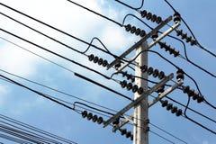 Polo de alto voltaje, posts de la electricidad con el cielo azul Foto de archivo