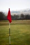 Polo de bandeira no fundo verde cênico do campo de golfe Foto de Stock