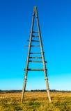 Polo de madeira da eletricidade velha do triângulo com céu azul Foto de Stock