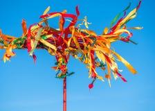Polo de madeira festivo para a escalada em Maslenitsa Fitas brilhantes que vibram no vento Imagem de Stock Royalty Free