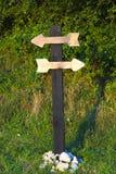 Polo de madera viejo con dos tablones de madera en la forma de flechas Imagen de archivo