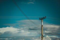Polo de poder de alto voltaje con el cielo azul Foto de archivo libre de regalías