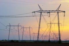 Polo de poder eléctrico de la torre en gran puesta del sol Imágenes de archivo libres de regalías