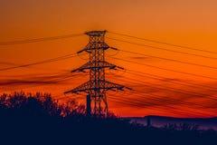 Polo eléctrico con los alambres eléctricos por la mañana Imagen de archivo
