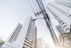 Polo eléctrico con los cables; casas en el fondo foto de archivo libre de regalías